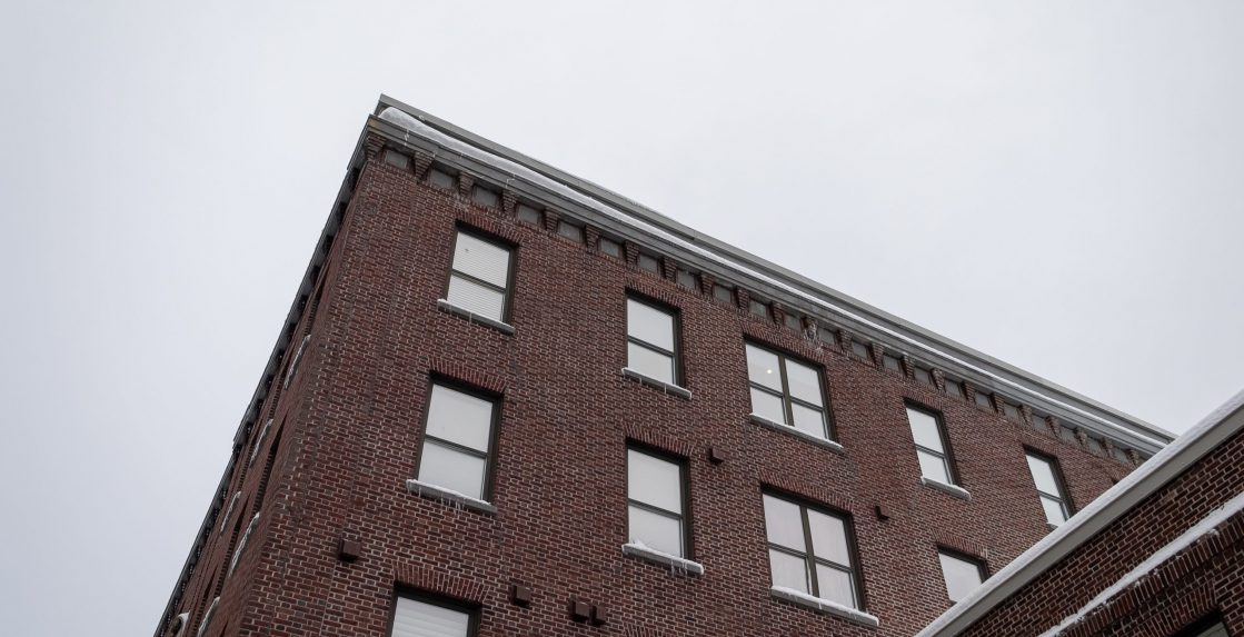 Participial corner view of three stories of a tall brown brick building with tall windows, ice hanging off the window sills and tan color decorative trim. The sky in the background is grey.